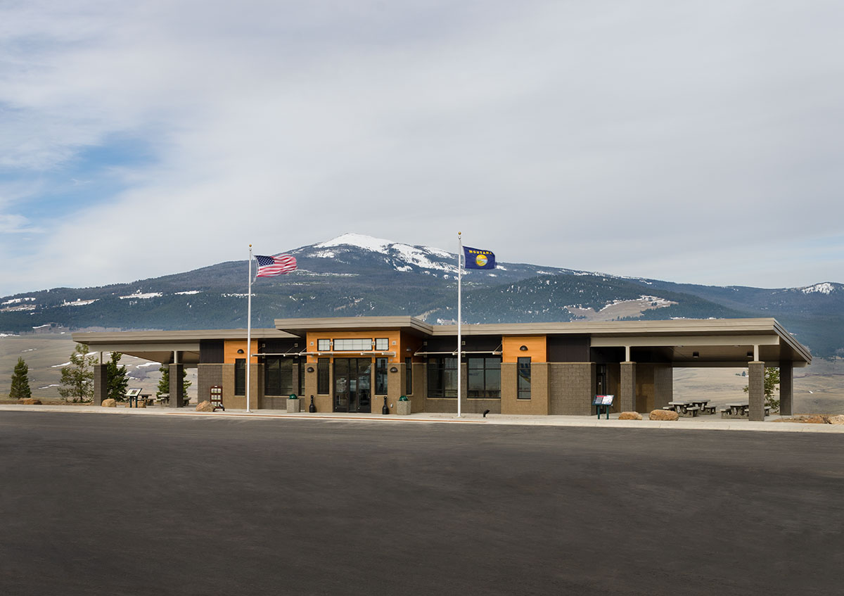 Montana rest area in Divide with the American flag and Montana flag in front of a snow covered mountain