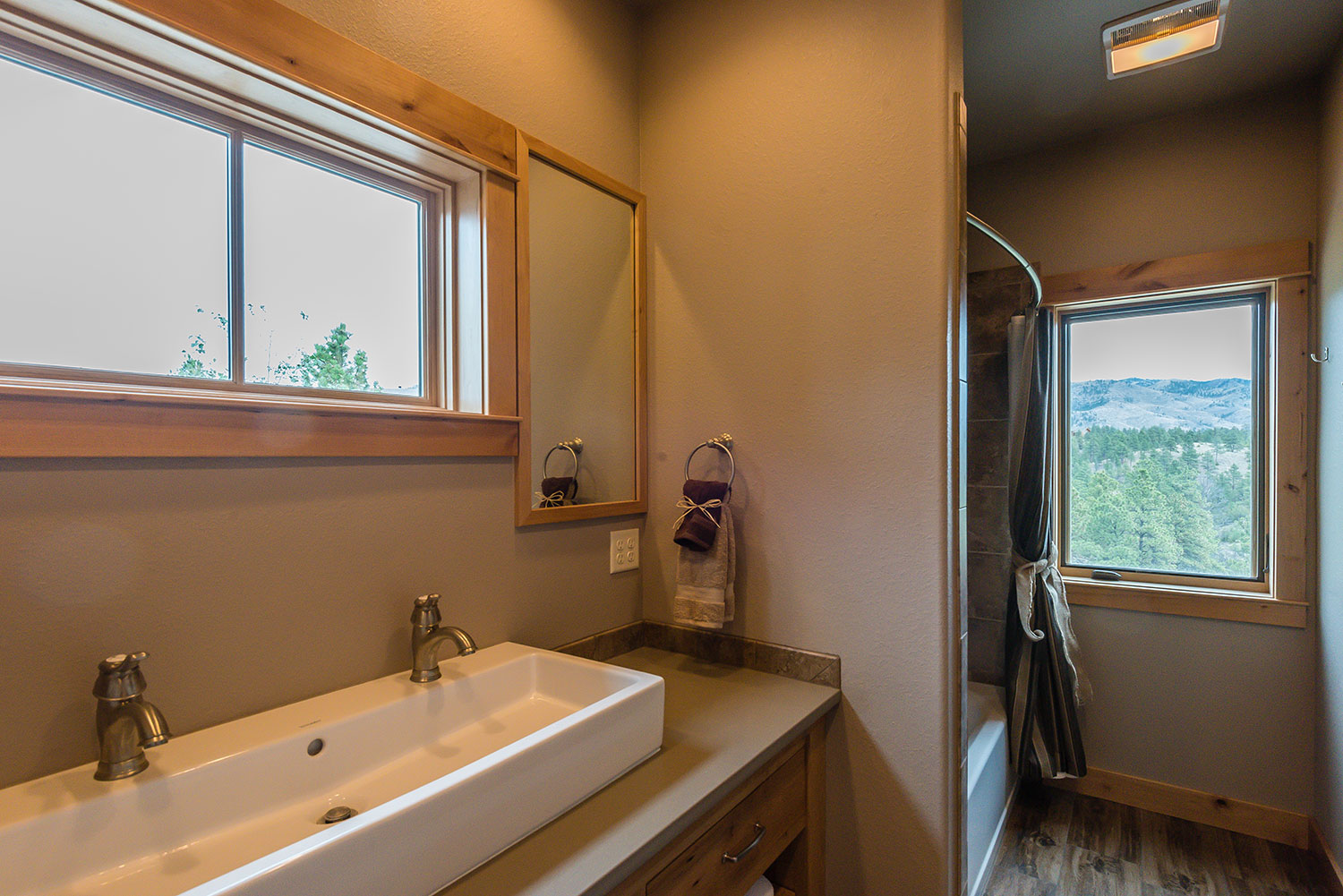 Bathroom with long rectangular sink with two faucets below a window with a shower and another window further back