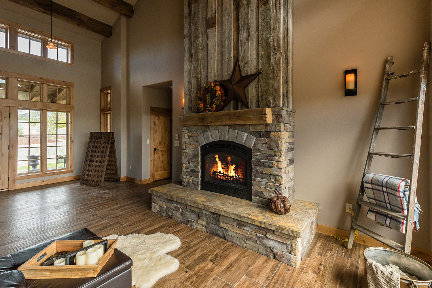 Rock-trimmed fireplace with rustic decor above and around it