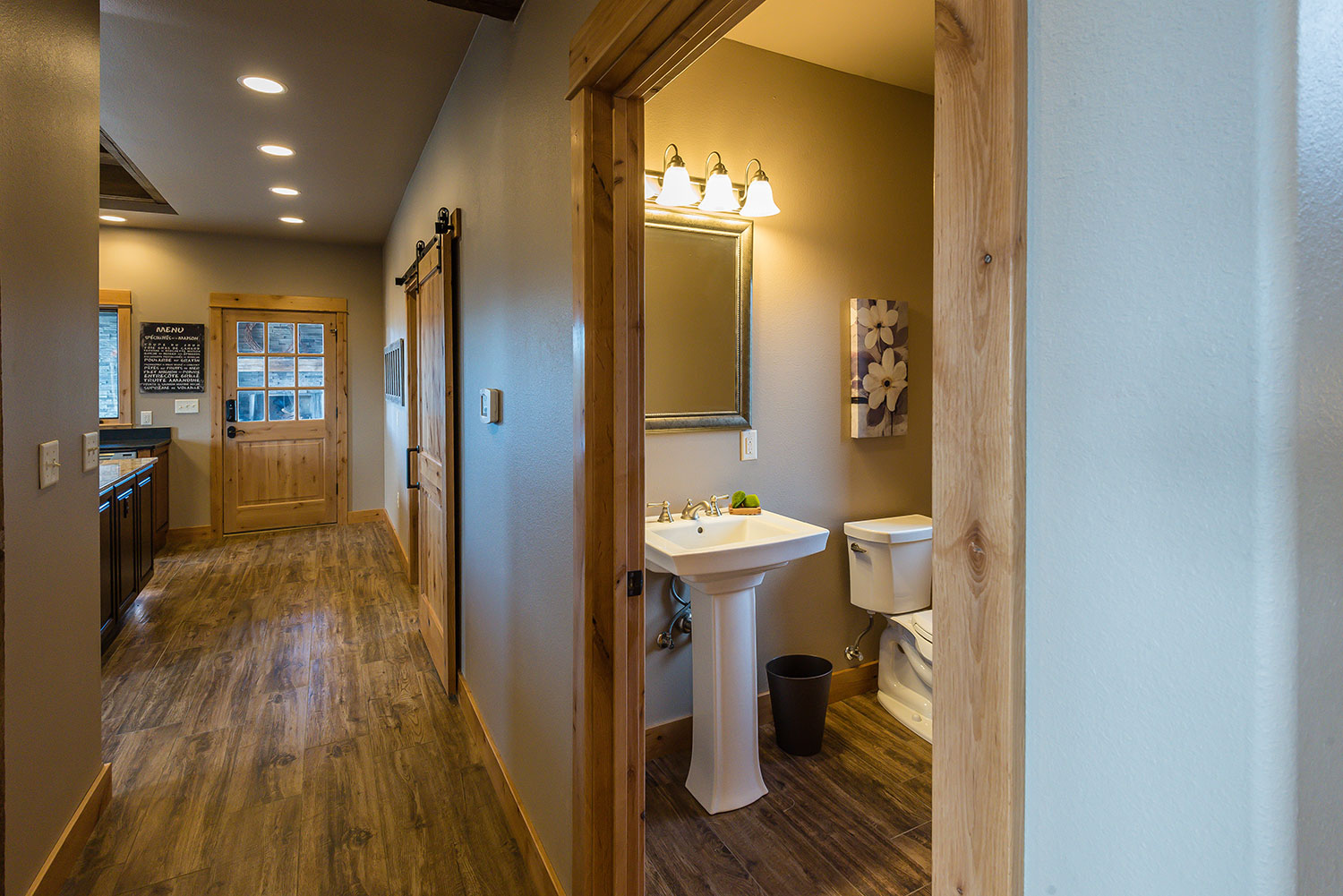 View down hallway into kitchen with a side view of a vanity with a pedestal sink and toilet in the bathroom