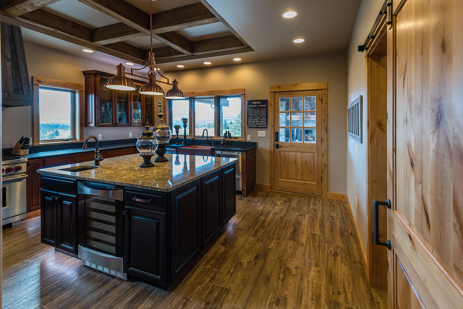 Rustic kitchen with granite countertops and copper farmhouse sink and exposed wood beams in ceiling