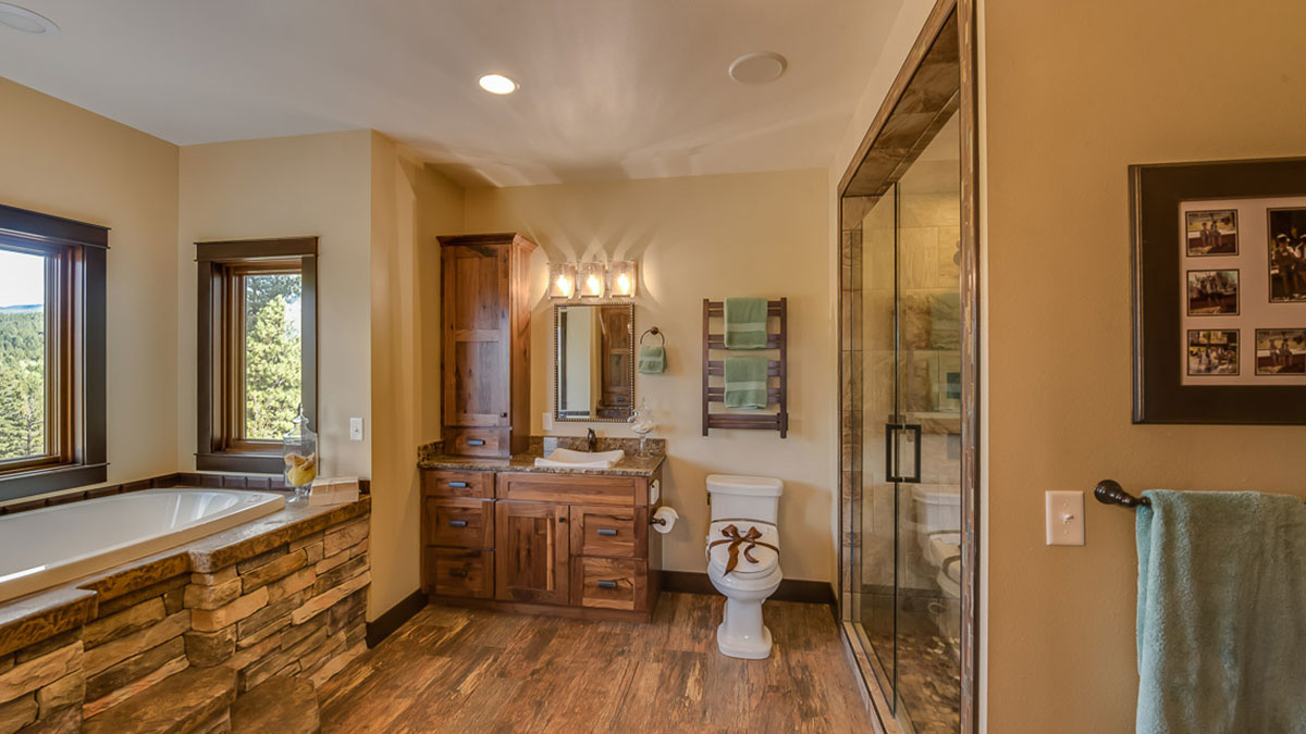 Bathtub off to the side with rock steps with a vanity in the center and a toilet with a bow on it next to a walk in shower