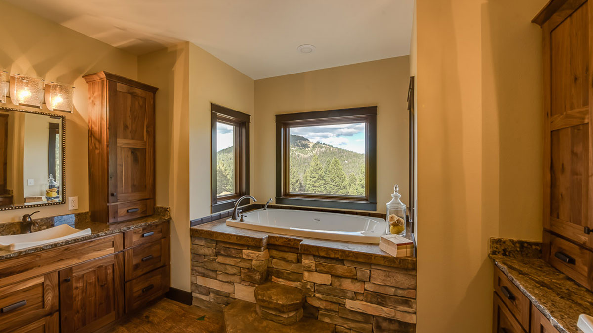 A large bathtub in a corner of the bathroom with granite around the top and rock steps up to it, with a view of a mountain