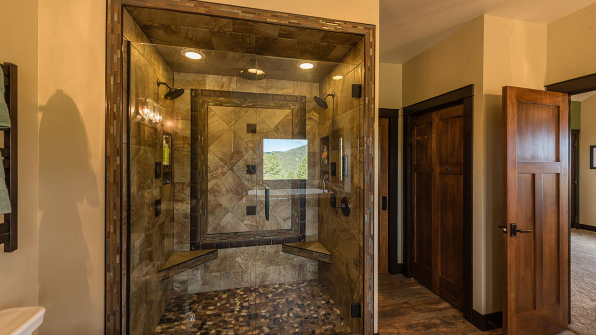 A large walk in shower with glass doors, two seats, a shower head on each side and lined with tile work and a rock floor