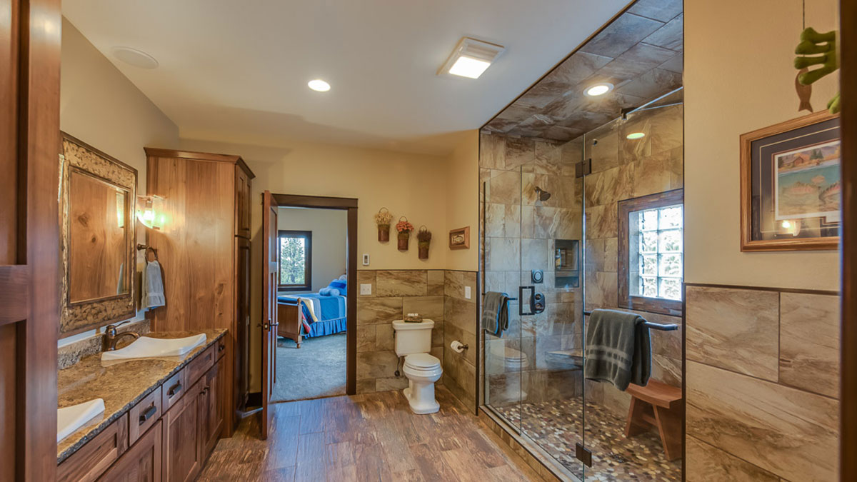 Bathroom with a walk in shower to the right and a granite countertop with custom sinks on the left with a view of the bedroom