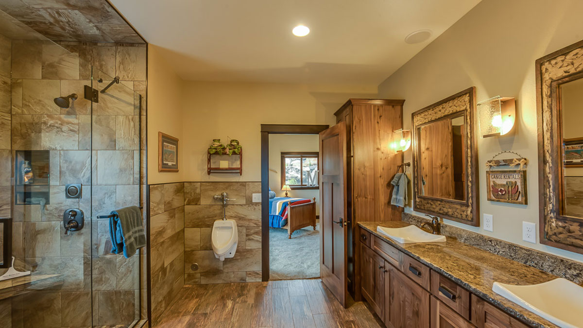 Bathroom with walk in shower to the left and a granite countertop with custom sinks on the right with a view of the bedroom