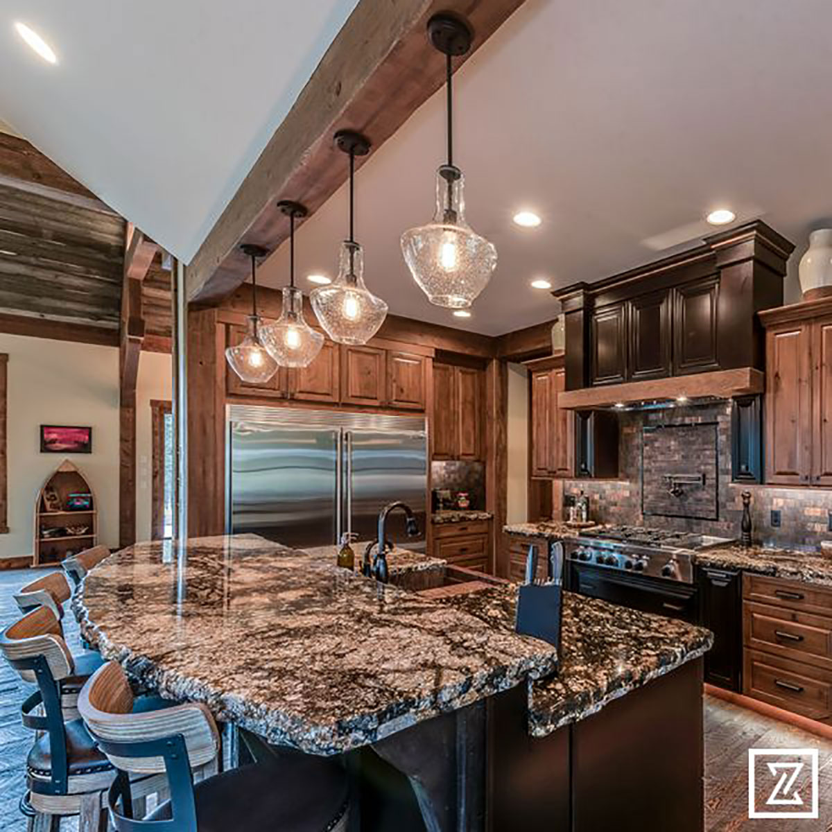 Well lit kitchen with hanging lights over the island with granite countertops and barstools around it