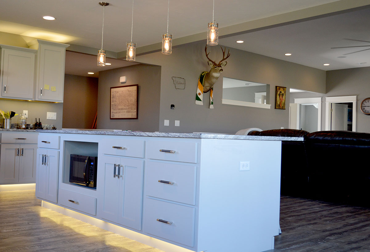 Well lit kitchen with a central island and hanging pendant lights and a view of the living room with a deer mount on the wall
